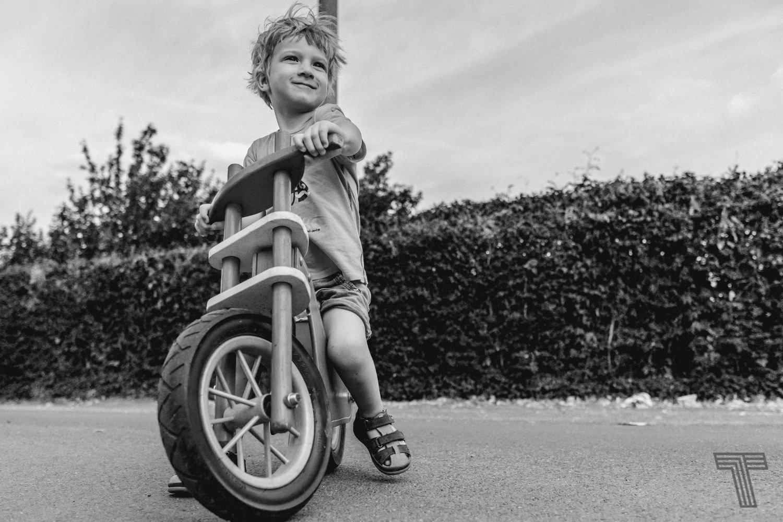 boy on strider bike looking proud