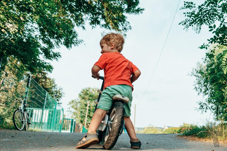 young boy on strider / kleiner junge auf laufrad