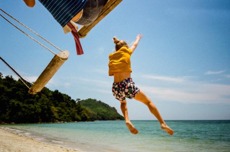 girl jumping off beach swing